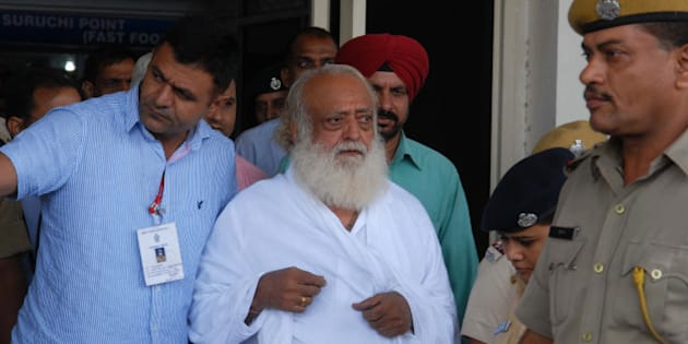 Indian spiritual guru Asaram Bapu (C) is escorted by police, after he was arrested from his Indore ashram, at the airport in Jodhpur on September 1, 2013. Police have arrested the  popular Indian spiritual guru for an alleged sexual assault on a 16-year-old schoolgirl at a religious retreat in central India, a local official said. AFP PHOTO/ STR        (Photo credit should read STRDEL/AFP/Getty Images)