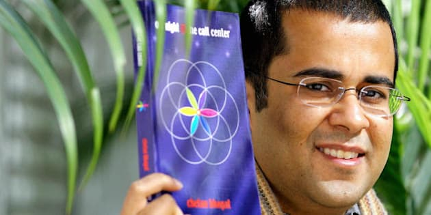 HONG KONG, CHINA:  Investment banker Chetan Bhagat poses with his novel in Hong Kong, 23 December 2005.  The book traces the story of six call center 'agents' whose difficult boss, unreasonable customers, and low self-esteem take such a huge toll on them that only a phone call from God can bail them out of the crisis.      AFP PHOTO / Samantha SIN  (Photo credit should read SAMANTHA SIN/AFP/Getty Images)