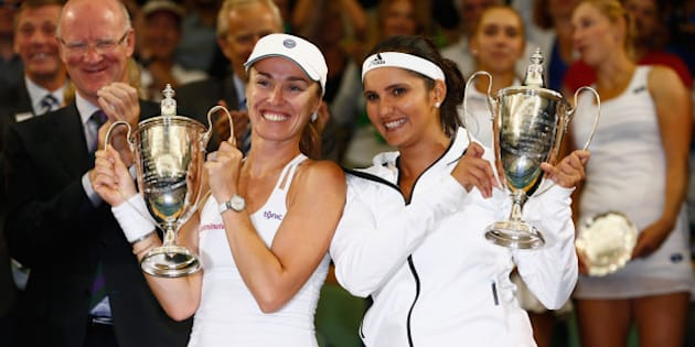 LONDON, ENGLAND - JULY 11:  Sania Mirza of India and Martina Hingis of Switzerland celebrate with the trophy after winning the Final Of The Ladies' Doubles against Ekaterina Makarova of Russia and Elena Vesnina of Russia during day twelve of the Wimbledon Lawn Tennis Championships at the All England Lawn Tennis and Croquet Club on July 11, 2015 in London, England.  (Photo by Julian Finney/Getty Images)