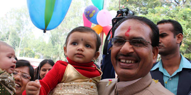 In this photograph taken on October 5, 2011, Chief Minister for the central Indian state of Madhya Pradesh Shivraj Singh Chouhan (R) poses with a child at a function to honour the 'girl child' in Bhopal. AFP PHOTO/STR (Photo credit should read STRDEL/AFP/Getty Images)