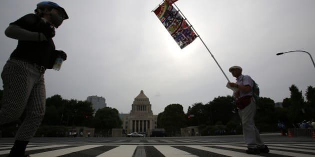 A protester holds a banner in front of the National Diet building during a rally in Tokyo, Sunday, June 14, 2015. About 25,000 protesters gathered outside parliament, opposing a set of controversial bills intended to expand Japan's defense role at home and internationally. (AP Photo/Shizuo Kambayashi)