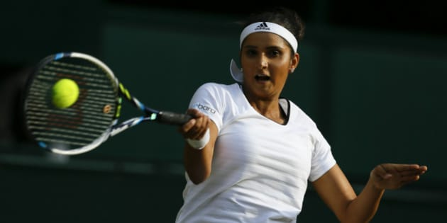 Sania Mirza of India plays a return during the women's doubles final between Martina Hingis of Switzerland, and Mirza, against Ekaterina Makanrova of Russia and Elena Vesnina of Russia at the All England Lawn Tennis Championships in Wimbledon, London, Saturday July 11, 2015. (AP Photo/Kirsty Wigglesworth)