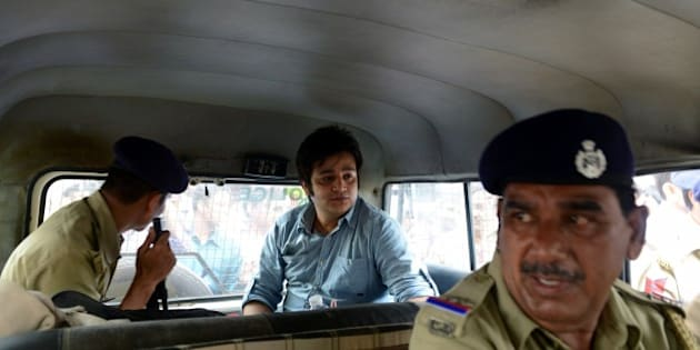 Vismay Shah (C) sits inside a police vehicle after a court sentenced him to five years in prison in a hit-and-run case in Ahmedabad on July 13, 2015. Shah, 27, was found guilty in case where his BMW car hit a two wheeler vehicle, killing two people. AFP PHOTO / Sam PANTHAKY        (Photo credit should read SAM PANTHAKY/AFP/Getty Images)