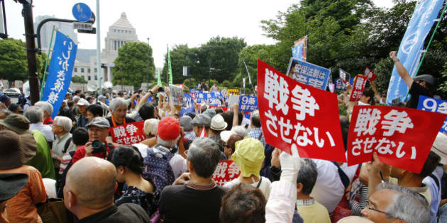 Protesters hold anti-war placards in front of the National Diet building during a rally in Tokyo, Sunday, June 14, 2015. About 25,000 protesters gathered outside the parliament, opposing a set of controversial bills intended to expand Japan's defense role at home and internationally. (AP Photo/Shizuo Kambayashi)