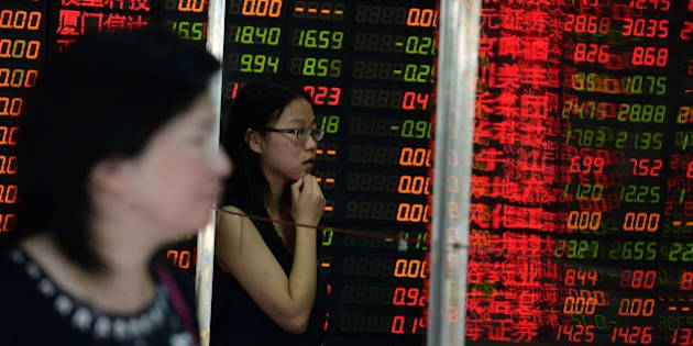 Investors check a screen displaying share prices at a security firm in Shanghai on July 6, 2015. Shanghai stocks were up 2.15 percent at midday on July 6 after the government unveiled its biggest package of measures so far to shore up the slumping market, but an initial surge was pared as analysts questioned their effect. CHINA OUT   AFP PHOTO        (Photo credit should read STR/AFP/Getty Images)