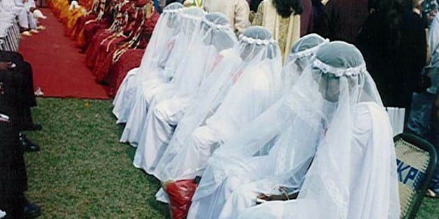 Christians in white wedding gowns, Muslims in red burqas, and Hindus in yellow sarees wait for a marriage ceremony at a mass wedding in Siliguri, India, Sunday Jan. 30, 2000.  Some153 couples were married. (AP Photo/Tarun Das)