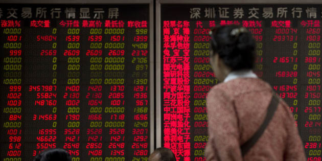 Chinese investors chat while monitoring stock prices at a brokerage house in Beijing Monday, July 13, 2015. Chinese authorities have accused securities firms of manipulating share prices and allowing improper trading during the country's market plunge, in a possible effort to deflect blame for investor losses totaling several trillion dollars. (AP Photo/Andy Wong)