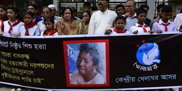 Bangladeshi protesters carry a banner during a demonstration against the lynching of a 13-year-old boy in Dhaka on July 14, 2015.  Outrage over the lynching of a 13-year-old boy mounted in Bangladesh July 14, 2015, with more protests over the murder which was captured on video, as one of the suspects confessed after being arrested in Saudi Arabia. Bangladeshi police have now arrested five people over the July 8 killing of Samiul Alam Rajon, who was tied to a pole and then subjected to a sickening assault in which he pleaded for his life. The 28-minute video of Samiul, which went viral after being posted on social media, has sparked an outpouring of anger, with petitions and demonstrations demanding the attackers face the death penalty. AFP PHOTO/ Munir uz ZAMAN        (Photo credit should read MUNIR UZ ZAMAN/AFP/Getty Images)