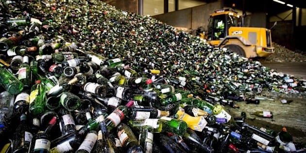 A bulldozer of a glass recycling processing plant makes a mountain of bottles in Gameren, following the Christmas and New Year celebrations, on January 2, 2015. AFP PHOTO/ANP/ KOEN VAN WEEL        (Photo credit should read Koen van Weel/AFP/Getty Images)