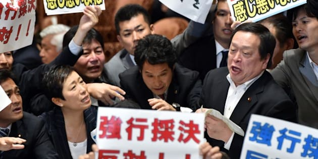 Yasukazu Hamada (2nd R), chairman of a parliamentary panel on Japanese Prime Minister Shinzo Abe's controversial security bills, is surrounded by opposition lawmakers holding placards which say 'Opposed to forced passage of the bills', during a parliamentary committee discussion on the bills at the National Diet in Tokyo on July 15, 2015.  Abe made another pitch on July 15 for security bills which would beef up Japan's military, as he pushed legislation through a key panel despite surging public and parliamentary opposition. The controversial bills that would expand the remit of the country's armed forces were approved by the lawmakers of the ruling coalition.   AFP PHOTO / Yoshikazu TSUNO        (Photo credit should read YOSHIKAZU TSUNO/AFP/Getty Images)