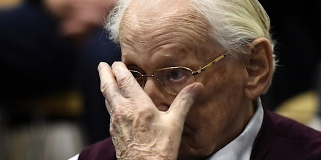 Convicted former SS officer Oskar Groening listens to the verdict of his trial on July 15, 2015 at court in Lueneburg, northern Germany. Oskar Groening, 94, sat impassively as judge Franz Kompisch said 'the defendant is found guilty of accessory to murder in 300,000 legally connected cases' of deported Jews who were sent to the gas chambers in 1944.  AFP PHOTO / POOL / TOBIAS SCHWARZ        (Photo credit should read TOBIAS SCHWARZ/AFP/Getty Images)
