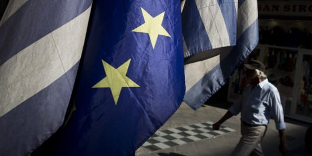 A man walks past a European and Greek flags in central Athens, on Tuesday, June 30, 2015. The European part of its international bailout expiring Tuesday and with it, any possible access to the remaining rescue loans it contains. As a result, the government is unlikely to repay a roughly 1.6 billion-euro ($1.87 billion) debt to the International Monetary Fund due Tuesday too. (AP Photo/Petros Giannakouris)