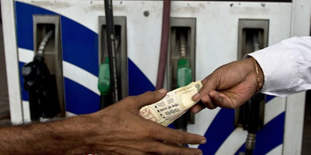 An Indian comsumer (R) pays a petrol-pump attendant in New Delhi on July 30, 2013. India's central bank kept its benchmark interest rates unchanged on July 30, ignoring demands for a cut as it seeks to defend the ailing rupee from a further devaluation.       AFP PHOTO/MANAN VATSYAYANA        (Photo credit should read MANAN VATSYAYANA/AFP/Getty Images)