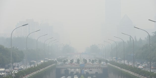 This picture taken on June 23, 2015 shows vehicles running in smog covered streets in Beijing. China's cities are often hit by heavy pollution, blamed on coal-burning by power stations and industry, as well as vehicle use. The issue has become a major source of popular discontent with the Communist Party, leading the government to vow to reduce the proportion of energy derived from fossil fuels. CHINA OUT     AFP PHOTO        (Photo credit should read STR/AFP/Getty Images)