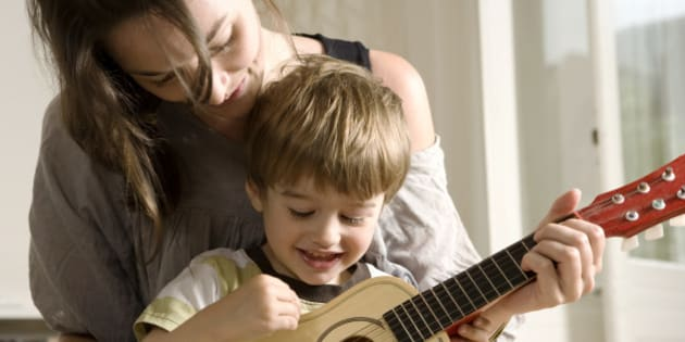 Young Mother Showing her Son how to Play Guitar