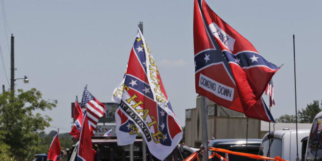 Confederate flag supporters fly their flags across the street from Durant High School, where President Barack Obama will be speaking, in Durant, Okla., Wednesday, July 15, 2015. (AP Photo/Sue Ogrocki)