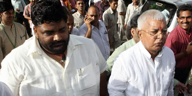 Member of Parliament from India's Rashtriya Janata Dal (RJD) Pappu Yadav (L), who is serving a life sentence in New Delhi's Tihar jail on charges of murdering a Communist Party of India-Marxist leader, walks along with RJD Chief and Indian Railway Minister Lalu Prasad Yadav (R) towards parliament house in New Delhi on July 22, 2008.   India's embattled coalition government will go into a parliamentary confidence vote with a tiny advantage but the margin is so tight it has no guarantee of surviving, Indian media say. The Congress party-led coalition government requires a simple majority to survive the vote after its left-wing allies withdrew support earlier this month over their opposition to a nuclear energy agreement with the United States. AFP PHOTO/PRAKASH SINGH (Photo credit should read PRAKASH SINGH/AFP/Getty Images)