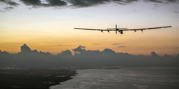 In this photo provided by Jean Revillard, Solar Impulse 2, a plane powered by the sun's rays and piloted by Andre Borschberg, approaches Kalaeloa Airport near Honolulu, Friday, July 3, 2015. His 120-hour voyage from Nagoya, Japan broke the record for the world's longest nonstop solo flight, his team said. (Jean Revillard/SI2 via AP)