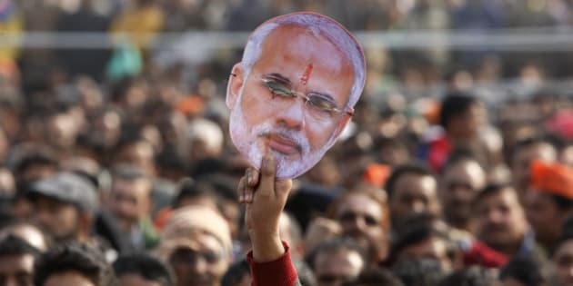 A supporter of India's ruling Bharatiya Janata Party (BJP) holds up a mask of Prime Minister Narendra Modi during an election campaign rally in Kathua, about 90 kilometers from Jammu, India, Saturday, Dec.13, 2014. The final two phases of the five-phased state elections of Jammu and Kashmir will be held on Dec. 14 and 20. (AP Photo/Channi Anand)
