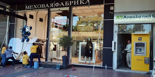 Workers replace the broken window of a fur shop in central Athens, on July 16, 2015 following last night's clashes during an anti-austerity protest. Early elections were inevitable in Greece, analysts and a minister said Thursday after Prime Minister Alexis Tsipras faced a mutiny from dozens of outraged government lawmakers as he passed creditor-mandated austerity reforms through parliament. AFP PHOTO/ LOUISA GOULIAMAKI        (Photo credit should read LOUISA GOULIAMAKI/AFP/Getty Images)