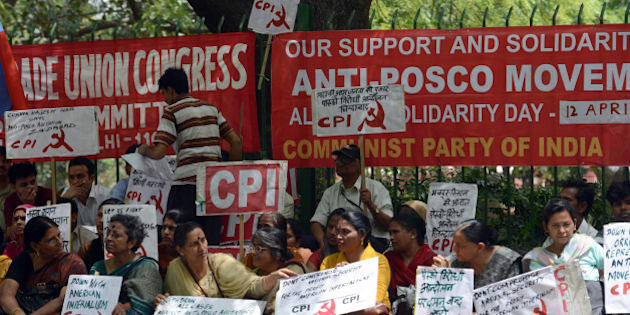 Hundreds of supporters from India's left parties hold anti-US,  Korean and Indian government placards against farmland being converted into an industrial development area during a protest against the American-Korean Posco steel plant in New Delhi on April 12, 2013. South Korean steel maker Posco is likely to start work on its much-delayed steel unit in Odisha within a year as the state has transferred a significant chunk of land required for the mega project to the firm, a senior government official said. AFP PHOTO/ RAVEENDRAN        (Photo credit should read RAVEENDRAN/AFP/Getty Images)