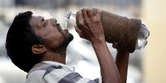 An Indian drinks water from a bottle on a hot summer day in Allahabad, India, Sunday, May 31, 2015. Heat-related conditions, including dehydration and heat stroke, have killed more than 2,000 people since mid-April in the southern Indian states of Andhra Pradesh and Telangana, according to state officials. (AP Photo/Rajesh Kumar Singh)