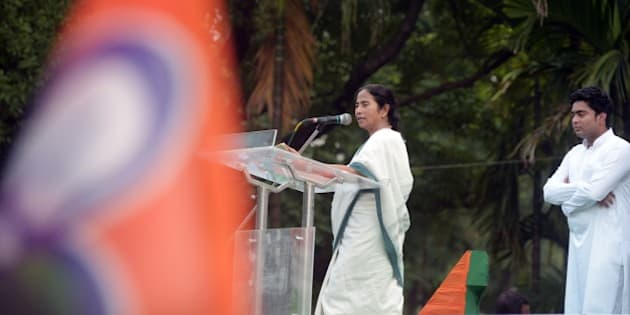 Chief minster of the eastern state of West Bengal and supremo of the Trinamool Congress, Mamata Banerjee (L), watched by party leader and nephew Abhishek Banerjee, delivers her speech after taking part in a rally organised to protest against the central government's Land Acquisition Bill in Kolkata on April 8, 2015.   The lower house of the Parliament in March 2015, passed the Right to Fair Compensation and Transparency in Land Acquisition, Rehabilitation and Resettlement (Amendment) Bill, 2015, with nine amendments. However, it was not passed in the Rajya Sabha where Prime Minister Narendra Modi's Bharatiya Janata Party (BJP) is in minority.  AFP PHOTO / Dibyangshu Sarkar        (Photo credit should read DIBYANGSHU SARKAR/AFP/Getty Images)