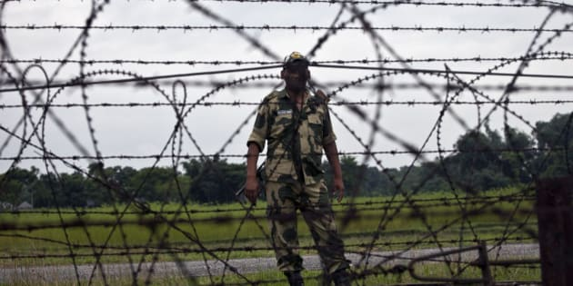 LALMONIRHAT DISTRICT, BANGLADESH - JULY 10: A member of the Indian BSF stands across from the India/Bangladesh border fence July 10, 2015 in Lalmonirhat District, Bangladesh. The India Bangladesh enclaves, also known as the chitmahals, are 162 parcels of land, each of which happens to lie on the wrong side of the India/Bangladesh border. There are 111 such Indian enclaves in Bangladesh and 51 Bangladeshi enclaves in India. On June 6th Bangladesh and India came to an agreement to let residents choose which country they want to belong to, and on July 31st these enclaves will dissolve into the country already surrounding them. For decades, these people have been stateless. Both the Bangladesh and Indian governments have refused to take responsibility for the enclave residents. Their villages do without public services, they cannot vote, and parents must forge documents to send their children to schools. Until the Enclaves Exchange Coordination Committee came to their enclaves this month, most Indian enclaves residents had never laid eyes on an Indian national before. (Photo by Shazia Rahman/Getty Images)