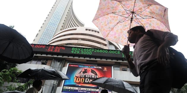 Indian residents walk past the Bombay Stock Exchange (BSE) during intra-day trading at a brokerage house in Mumbai on September 1, 2014. The benchmark 30 share BSE index Sensex rose 262.19 points to hit new lifetime high of 26,900.30.  AFP PHOTO / INDRANIL MUKHERJEE        (Photo credit should read INDRANIL MUKHERJEE/AFP/Getty Images)