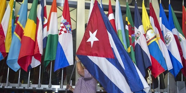 Workers at the US Department of State add the Cuban flag at to the display of flags inside the main entrance at 202 'C' Street at 4am local time (0800 GMT) in Washington, DC on July 20, 2015. The United States and Cuba formally resumed diplomatic relations on July 20, as the Cuban flag was raised at the US State Department in a historic gesture toward ending decades of hostility between the Cold War foes.      AFP PHOTO / Paul J. Richards        (Photo credit should read PAUL J. RICHARDS/AFP/Getty Images)
