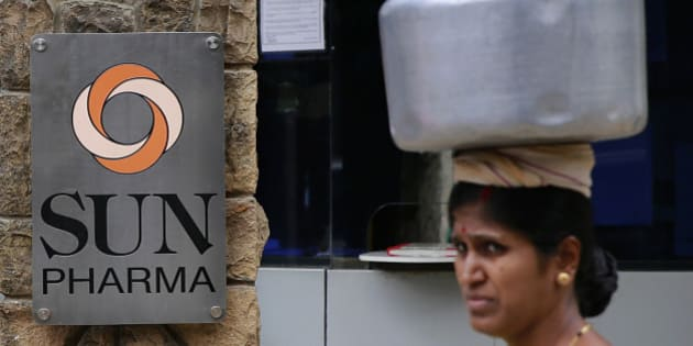 An Indian woman carries a water vessel as she walks past the office of Sun Pharmaceutical in Mumbai, India, Monday, April 7, 2014. The Sun Pharmaceutical Industries is buying troubled generic drugmaker Ranbaxy Laboratories in a $4 billion all-stock transaction, the companies said Monday. (AP Photo/Rafiq Maqbool)