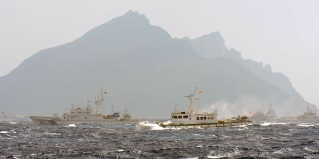 A Taiwan Coast Guard boat (R-with red flag) is blocked by a Japan Coast Guard vessel (L) in the waters near the disputed Diaoyu / Senkaku islands in the East China Sea on September 25, 2012.  Coastguard vessels from Japan and Taiwan duelled with water cannon after dozens of Taiwanese boats escorted by patrol ships sailed into waters around Tokyo-controlled islands.  Japanese coastguard ships sprayed water at the fishing vessels, footage on national broadcaster NHK showed, with the Taiwanese patrol boats directing their own high-pressure hoses at the Japanese ships.     AFP PHOTO / Sam Yeh        (Photo credit should read SAM YEH/AFP/GettyImages)