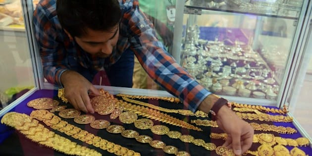 An Indian trader adjusts jewellry displayed during the Hyderabad Jewellery Pearl and Gem Fair (HJF) in Hyderabad on June 5, 2015. Over 150 exhibitors will show diamond and gold jewellery at the HJF fair in the city from June 5-7, 2015. AFPHOTO/ Noah SEELAM        (Photo credit should read NOAH SEELAM/AFP/Getty Images)
