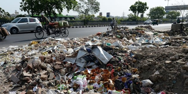 Heap of garbage are strewn along the roadside as sanitation workers strike in New Delhi on June 11, 2015.  Sanitation workers with Municipal Corporation of Delhi (MCD), who are on strike over non-payment of salaries for the last three months, have dumped garbage at traffic intersections.  AFP PHOTO/PRAKASH SINGH        (Photo credit should read PRAKASH SINGH/AFP/Getty Images)