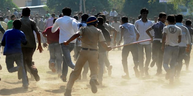 An Indian policeman (C) runs towards a crowd with a lathi stick outside The Vidarbha Cricket Association (VCA) Cricket Stadium in Nagpur on March 8, 2011, as supporters queued for tickets ahead of the forthcoming Cricket World Cup 2011 match between India and South Africa which is scheduled to take place on March 12.  Ticket-hungry fans, desperate to see India's World Cup clash against South Africa, were baton-charged by police as they queued, reports claimed. The clashes happened outside the Vidarbha Cricket Association ground, the venue for the Group B game, as police struggled to control the crowds, the CNN-IBN television station reported.  AFP PHOTO/STR (Photo credit should read STRDEL/AFP/Getty Images)