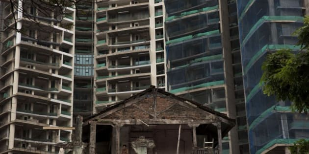 In this Sept. 8, 2014 photo, an Indian man watches from the balcony of a broken house as new high-rise apartments are seen in the background, in Mumbai, India.  About 80 percent of the 3.6 billion people in developing Asian countries still live on less than $5 a day, many relying on day labor, rag picking or other meager livelihoods. Even migrants who arrived in cities years ago feel trapped in a seemingly permanent underclass. (AP Photo/Bernat Armangue)