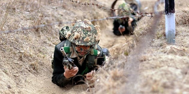 Indian Border Security Force (BSF) woman commandos crawl under barbed wire during an excercise at the Kharkan Training Camp at Hoshiarpur, around 60 kms from Jalandhar on January 13, 2015.   The Border Security Force (BSF) is a paramilitary force charged with guarding India's land border during peace time and preventing transnational crime.   AFP PHOTO / SHAMMI MEHRA        (Photo credit should read SHAMMI MEHRA/AFP/Getty Images)