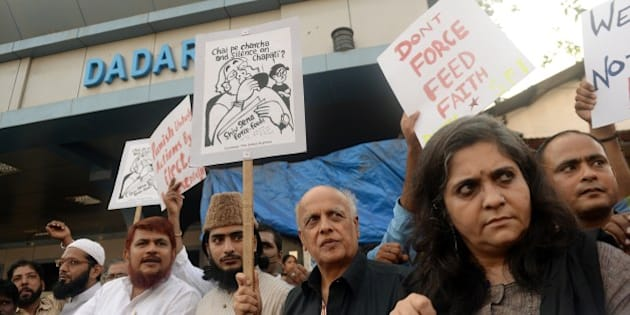 Indian Bollywood director Mahesh Bhatt (3rd R) and Indian activists hold placards during a protest against the Shiv Sena party in Mumbai on July 24, 2014. Television footage on July 23 showed a hardline Hindu nationalist party Shiv Sena lawmaker (member of parliament) apparently trying to force-feed a Muslim man during the fasting month of Ramadan. AFP PHOTO/ PUNIT PARANJPE        (Photo credit should read PUNIT PARANJPE/AFP/Getty Images)