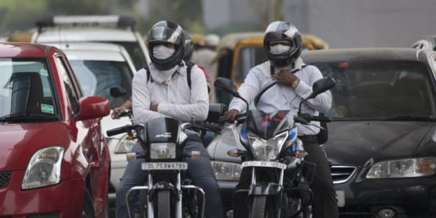 Motorists cover their faces to protect themselves from air pollution in New Delhi, India, Tuesday, June 16, 2015. Never mind lowering the rate of death from air pollution in India and China. Just keeping those rates steady will demand urgent action to clear the skies, according to a new report published Tuesday. (AP Photo/Tsering Topgyal)