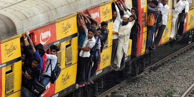 Commuters hang onto an overcrowded suburbun railway train on the Central Railway (CR) line in Mumbai on April 19, 2012.   Three people were killed and around 14 were injured when they fell off a moving suburbun train on the CR line. Thousands of commuters in Mumbai had a harrowing time as services on the Central Railway line were thrown out of gear following a fire in a signal cabin between two suburbun railway stations on Tuesday night causing heavy damage to signalling gears.  Mumbai's suburban trains or 'locals' carry an estimated seven million people every day and are a lifeline in an overcrowded city with traffic-clogged, potholed roads. Train doors are normally open to the elements to combat high temperatures and humidity, with many travellers also hanging out of carriages or perching between them.   AFP PHOTO/Indranil MUKHERJEE (Photo credit should read INDRANIL MUKHERJEE/AFP/Getty Images)