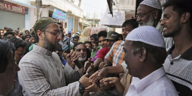 All India Majlis Ittehadul Muslimeen (AIMIM) president Asaduddin Owaisi, left, contesting in the parliamentary elections greets people during his campaign in Hyderabad, India, Friday, April 11, 2014. Indians voted in the crucial third phase of national elections Thursday, with millions going to the polls in the heartland states that are essential to the main opposition Hindu nationalist party's bid to end the 10-year rule of Congress party. (AP Photo/Mahesh Kumar A.)