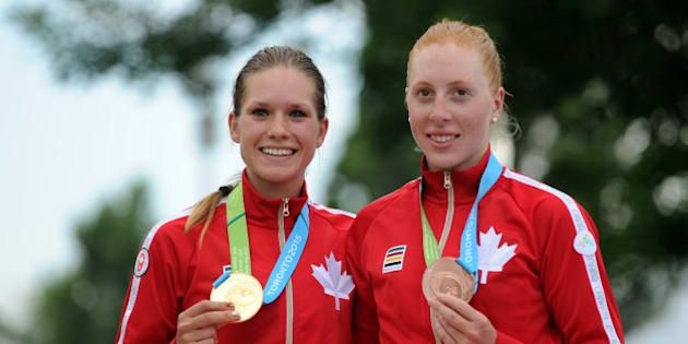 Canadians Jasmin Glaesser (L), gold,  and Allison Beveridge (R), bronze, pose with their medals during the awards ceremony for  the Women's Cycling Road Race at the 2015 Pan American Games in Toronto, Canada July 25, 2015. AFP PHOTO / HECTOR RETAMAL        (Photo credit should read HECTOR RETAMAL/AFP/Getty Images)