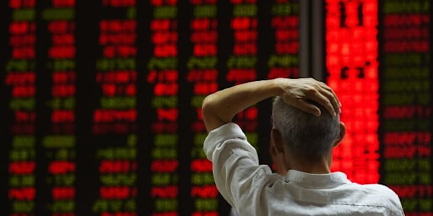 An investor looks at screens showing stock market movements at a securities company in Beijing on July 14, 2015. Hundreds of firms were expected to resume trading again on July 14, adding to the more than 400 that returned July 13, after they were suspended over the past few weeks to prevent a market meltdown. Authorities intervened after the Shanghai index plunged 30 percent in three weeks, wiping trillions of dollars from market capitalisations, spreading contagion in regional markets and raising fears over the potential impact to the real economy. AFP PHOTO / GREG BAKER        (Photo credit should read GREG BAKER/AFP/Getty Images)