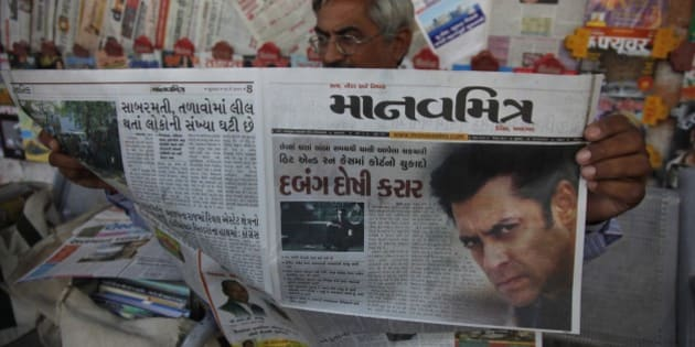 An Indian man reads a newspaper that has the news of Bollywood actor Salman Khan's court verdict on the front page in Ahmadabad, India, Wednesday, May 6, 2015. One of India's biggest and most popular movie stars, Khan, was sentenced to five years in jail Wednesday on charges of driving a vehicle over five men sleeping on a sidewalk and killing one in a hit-and-run case that has dragged for more than 12 years. (AP Photo/Ajit Solanki)