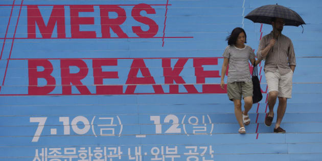 "A couple passes by letters on the stairs to advertise a festival called ""MERS(Middle East Respiratory Syndrome) Breaker"" to hope an end to the MERS outbreak at the Sejong Culture Center in Seoul, South Korea, Sunday, July 12, 2015. South Korean letters read "" The Sejong Culture Center. "" (AP Photo/Ahn Young-joon)"
