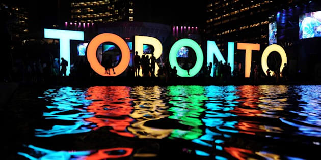 The Toronto sign is seen at the Nathan Phillips Square as people watch a concert during 2015 Pan American Games in Toronto, Canada on July 13, 2015. AFP PHOTO/HECTOR RETAMAL        (Photo credit should read HECTOR RETAMAL/AFP/Getty Images)