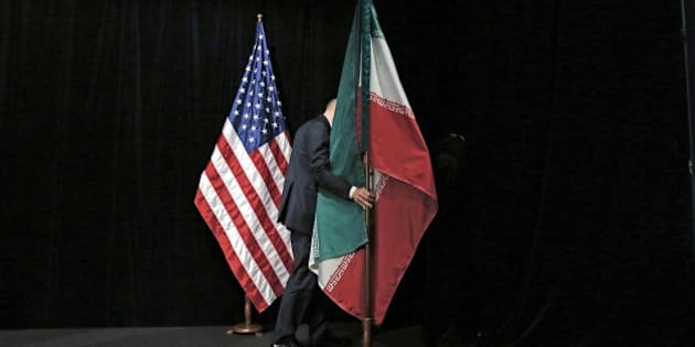 A staff removes the Iranian flag from the stage after a group picture with foreign ministers and representatives of Unites States, Iran, China, Russia, Britain, Germany, France and the European Union during the Iran nuclear talks at the Vienna International Center in Vienna on July 14, 2015. Iran and six major world powers reached a nuclear deal on Tuesday, capping more than a decade of on-off negotiations with an agreement that could potentially transform the Middle East, and which Israel called an 'historic surrender'.  AFP PHOTO / POOL / CARLOS BARRIA        (Photo credit should read CARLOS BARRIA/AFP/Getty Images)
