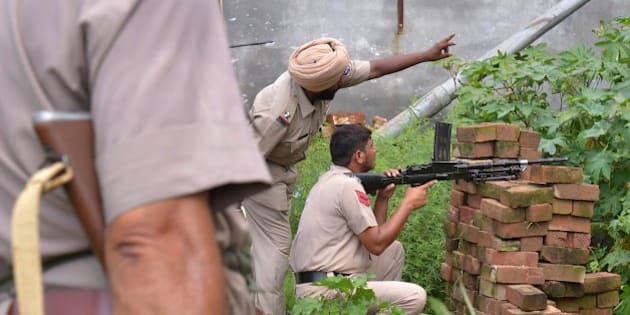Indian Punjab police personnel take position during an encounter with armed attackers at the police station in Dinanagar town, in the Gurdaspur district of Punjab state on July 27, 2015. Indian security forces were  battling an armed attack on a police station near the Pakistan border in which at least five people have been killed.   AFP PHOTO/ NARINDER NANU        (Photo credit should read NARINDER NANU/AFP/Getty Images)