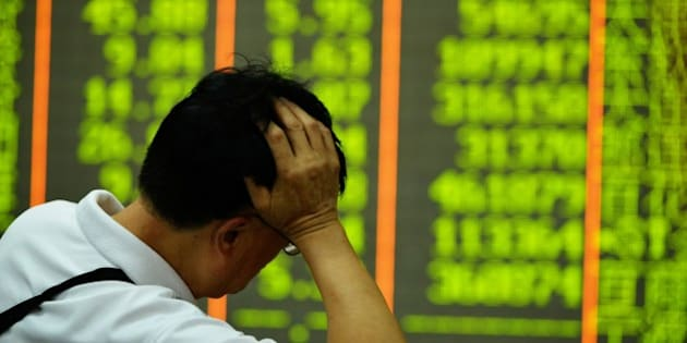 An investor rests on his arm before a screen that shows share prices in a security firm in Hangzhou, east China's Zhejiang province on July 27, 2015.  China's benchmark Shanghai stock index slumped 5.22 percent in afternoon trade on July 27, dragged lower by worries over the economy.    AFP PHOTO    CHINA OUT        (Photo credit should read STR/AFP/Getty Images)