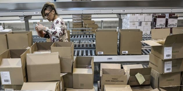 An employee processes orders in the new 10,000 m2 warehouse of online private sales website 'vente-privee.com' in Montagny-les-Beaune, central-eastern France, on April 17, 2015. The new site can process up to 10,000 orders a day, and is dedicated to gastronomy and wine business.  AFP PHOTO / JEAN-PHILIPPE KSIAZEK        (Photo credit should read JEAN-PHILIPPE KSIAZEK/AFP/Getty Images)